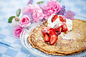 Fried pancakes with strawberries and whipped cream