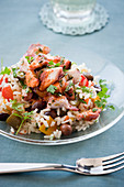 Mediterranean rice salad with octopus, olives and peppers