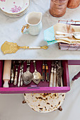 Silver cutlery in open drawer of kitchen table