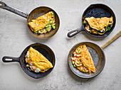 Vier Omelett-Variationen (Lachs, Avocado, Spinat und Champignons, scharfe Asia-Garnelen)