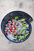 Tomato and mushroom skewers and green peppers on a barbecue