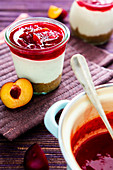 Layered desserts with cream cheese, plum compote and biscuit crumbs