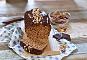 Vegan nut cake with walnuts, pecans and chocolate icing