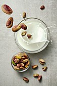 Pistachios falling into a glass of milk
