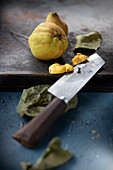 Quince on a wooden board with a chef's knife