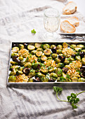 A baking tray with vegan duchess potatoes, baked brussels sprouts and wild mushrooms