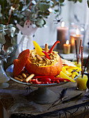 Halloween-Kürbis mit Hummusfüllung und Gemüsesticks
