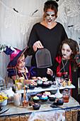 Verkleidete Frau und Kinder bei einer Halloween-Party
