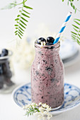 A smoothie with blueberries and elderflowers