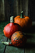 Three different pumpkins on a wooden background