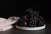 Autumn fruits: red grapes, blackberries and plums on plates