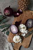 Garlic and red onions on a wooden chopping board