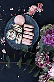 Two kinds of macarons on plates, beside peony blossoms