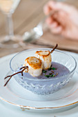 A scallop skewer on purple potato and coconut cream