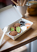 Green falafel with various dips in a takeaway box