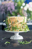 Cake with white chocolate icing and edible flowers