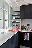 Kleine moderne Küche im Loftstil mit schwarzen Metall-Schrankfronten