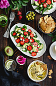 Summer salad with vegetables and strawberries, a dip and crackers