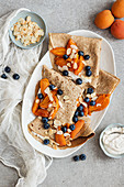 Crepes with ricotta, apricots, blueberries and flaked almonds