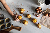 From above crop person hand holding a homemade cupcakes on wooden table with arranged eggs