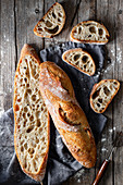 From above whole and halved appetizing baguettes arranged on white towel against rustic wooden background
