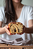 Crop female cook holding fresh twisted bread or cinnamon babka over wooden table with striped towel on blurred background