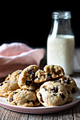 Plate of tasty vegan cookies with chocolate chips placed on lumber table near blurred milk and cloth against black background