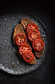 Geröstete Brotscheiben belegt mit Tomatenscheiben