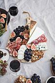 Käseplatte zum Picknick serviert mit Früchten, Nüssen und Rotwein