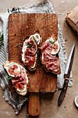 Crostini mit Feigen, Parmaschinken und Ricotta auf Holzbrett