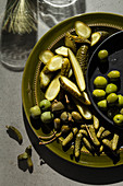A selection of pickled gherkins, caper berries and green olives on an olive green plate