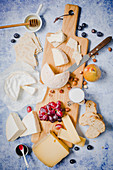 A cheese board with fruits, bread and honey
