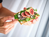 Crop person holding homemade colorful open sandwich with slices of fig and pieces of cheese on crisp rye bread
