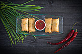 Spring rolls with a chili dip and chives (Asia)