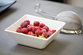 Fragrant appetizing fresh raspberry with green stem in white square bowl and metal sieve with handle on table