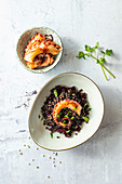 Black fregola (button pasta, Sardinia) with beetroot and squid
