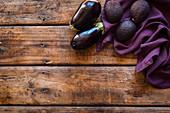 Lila Gemüse: Avocados und Auberginen auf violettem Tuch