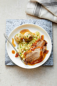 Crispy pork in a beer sauce with pretzel dumplings and bavarian cabbage