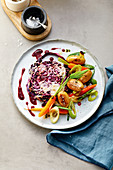 Red cabbage steak with small potatoes and spring vegetables