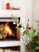 Christmas decorations hung from string in front of fireplace