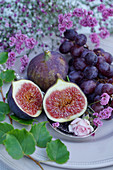 Fresh figs and grapes surrounded by flowers