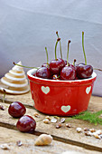Cherries in a red ceramic bowl decorated with hearts