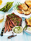Barbeque flank steak with asparagus, herb butter and grilled bread