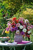 Strauß aus Dahlien, Zinnien und Federborstengras, Schale mit Blüten im Wasser