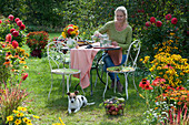 Frau sitzt am Tisch im Garten zwischen Beeten mit Dahlien, Scheinsonnenhut, Sonnenbraut und Sonnenhut, Korb mit Äpfeln und Weintrauben