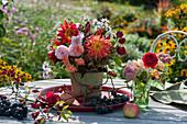 Sträuße aus Dahlien, Rosen, Astern und Fetthenne, Weintrauben und Hagebutten als Deko