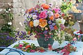 Bunter Herbststrauß aus Rosen, Astern, Fetthenne, Schneebeeren, Dahlie und Pfaffenhütchen, Zweig mit Hagebutten