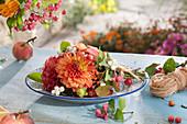 Strauß als Tellerdeko: Dahlien, Knallerbsen, Hagebutten, Pfaffenhütchen und Zieräpfel