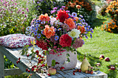 Bank mit Herbststrauß aus Dahlien, Astern, Rosen, Fetthenne und Pfaffenhütchen