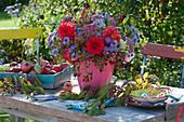 Strauß aus Dahlien, Astern, Fetthenne, Hagebutten und Pfaffenhütchen, Tablett mit Äpfeln, Zweig vom Zierapfel als Deko